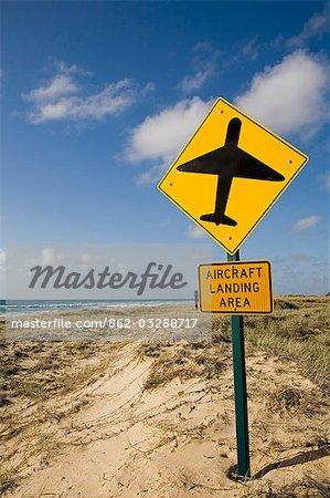 Un signe rappelle aux automobilistes que la route sable de plage Seventy - five Mile sur l'île de Fraser est également une piste d'atterrissage pour petits avions.