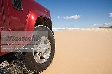 Quatre roues sur la route de sable de la plage Seventy - five Mile sur la côte est de l'île Fraser. Plus grande île de sable du monde n'a aucuns routes pavées et peut seulement être parcourue en 4x4.