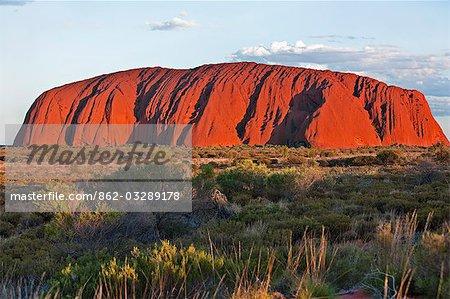 Australie, Northern Territory. Uluru ou Ayres Rock, une formation rocheuse de grès énormes, est l'une des icônes naturelles plus reconnus de l'Australie. Le rocher semble changer de couleur dans les différentes lumières.