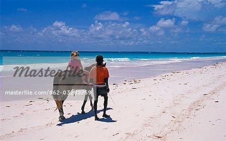 Jeune fille équitation le long de la plage de sable rose sur Harbour Island, Bahamas