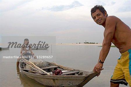 Un père et son fils partent pour une pêche de journée de leur dug out canoe sur le Rio Tapajos, un affluent du fleuve Amazone, au coucher du soleil dans la région d'Amazonas Brésil