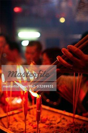 Ein Besucher Lichter Räucherstäbchen am buddhistischen Schrein in den Man Mo Tempel in Sheung Wan, Hong Kong Island