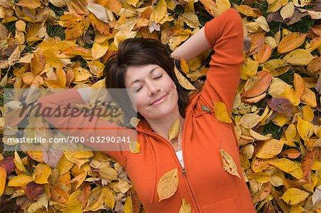 Femme couchée sur les feuilles d'automne