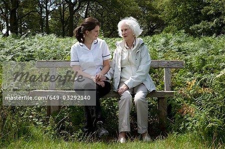 Nurse holding hand of elderly woman
