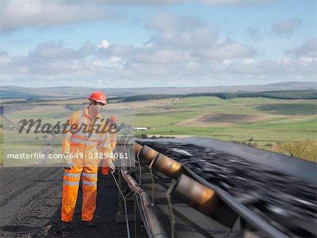 Arbeitnehmer überprüfen von Kohle auf Förderband