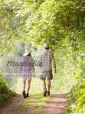 couple in hats walking along track