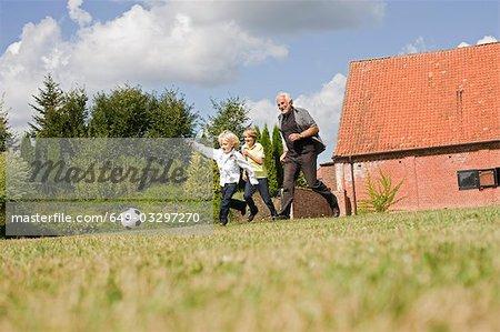 grand-père et enfants jouant au football