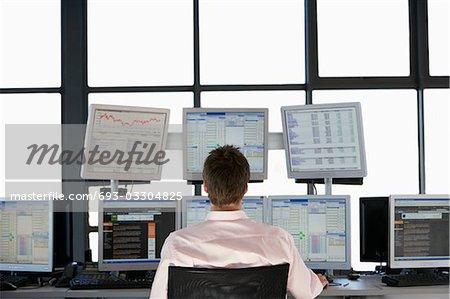 Hommes d'affaires assis au comptoir, je regarde les écrans d'ordinateur, vue arrière.