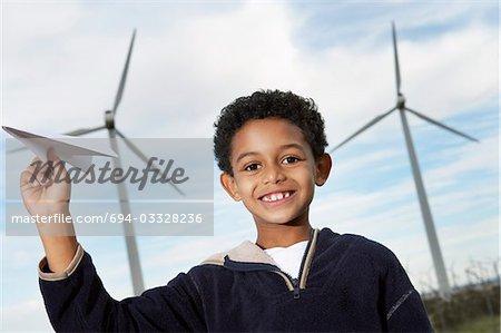 Junge (7-9) spielen mit Papierflieger am Windpark, Porträt