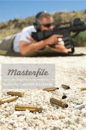 Man aiming machine gun at firing range, focus on bullets in foreground