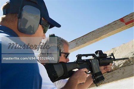 Instructeur avec l'homme qui vise la mitrailleuse à tir