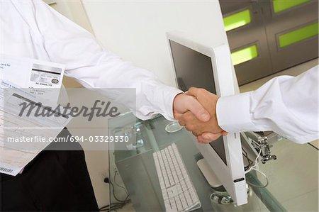 Les hommes d'affaires lui serrer la main