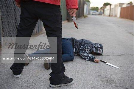 Homme debout à côté de l'homme poignardé gisant sur le sol