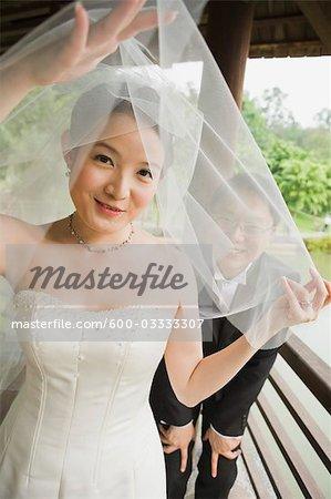 Bride and Groom Peeking Through Veil