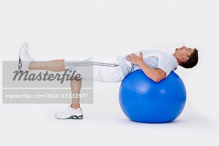 Ein Mann mit einem Gymnastikball Dehnung