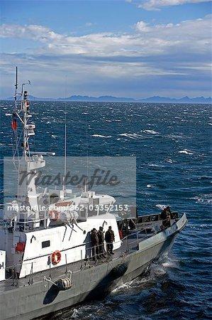 Chili, Tierra del Fuego. Un bateau-pilote marine chilienne répond à un navire de l'expédition qu'il entre dans le détroit de Magellan, la route pour le port de Puerto Williams au sud de l'Isla Grande de Tierra del Fuego avec le Cap Horn en arrière-plan.