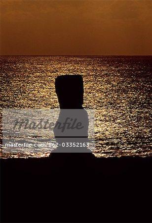 Chili, île de Pâques, Tahai. À Ahu Kote Riku, un seul moai bien conservé se détache au coucher du soleil car elle se situe sur le dessus de le trois ahus ou plates-formes de centre cérémoniel de Tahai. Tahai est juste à quelques pas de la principale agglomération de l'île de Pâques, Hanga Roa sur la côte ouest de l'île, soutenu par l'océan Pacifique.