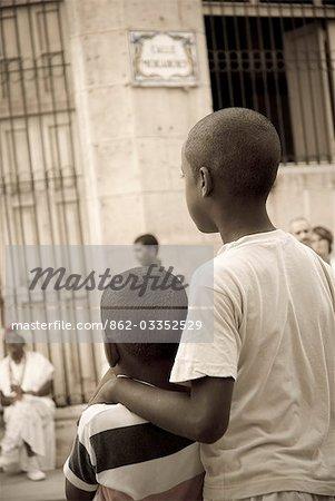 Cuba, la Havane. Garçons regardant impromtu street parade, Plaza Vieja