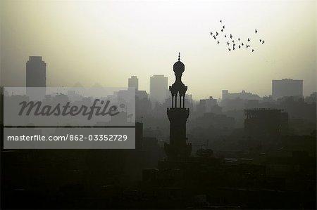 Découvre au Caire depuis le sommet de la mosquée bleue, l'ouest à travers le Caire modern et les pyramides au loin. Le Caire est aujourd'hui une des plus grandes villes du monde avec plus de 18 millions de personnes.