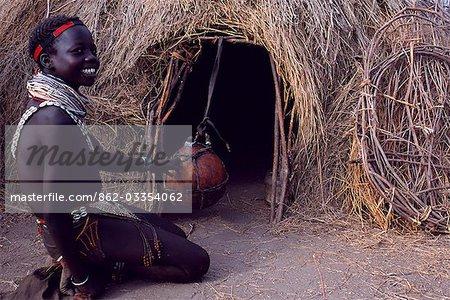 Une fille Nyangatom barattes à beurre dans une gourde suspendue à l'entrée de sa hutte. Typique de sa tribu, elle porte des couches multiples de perles en colliers et un jupe de veau finement perlée. Le Nyangatom ou Bume sont une tribu nilotique de pasteurs semi-nomades qui vivent le long des rives du fleuve Omo dans le sud-ouest de l'Éthiopie.