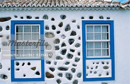 Détail des fenêtres sur une maison blanchies à la chaux avec incrustation de pierres volcaniques et un cadre bleu dans la Garafia de Saint-Domingue