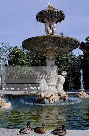 Mallard ducks sit beside a classical fountain in the Retiro Park