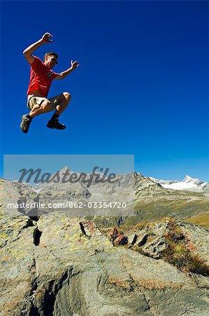 Hiker jumping high on trails at Schwarzee Paradise,Zermatt,Valais,Switzerland