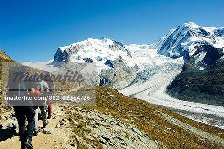 Hikers nearing ice flow of the Monte Rosa glacier,Zermatt,Valais,Switzerland
