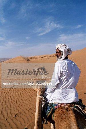 Un Bedu chevauche son chameau dans le désert