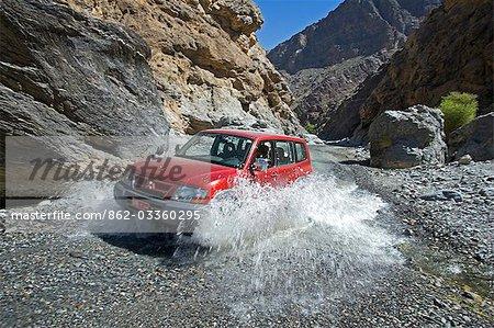 Oman, montagnes de Hajar de Western, Wadi Bani Awf. Un quatre roues motrices rend dans un autre passage de la rivière Oued rejoindre un village intérieur.