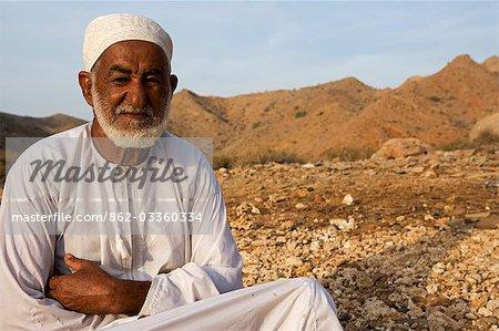 Oman, Mascate région, Bandar Khayran. Un vieux fermier s'assied pour un chat habillé en costume omanais traditionnel.