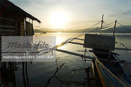 Philippines,Palawan,Puerto Princessa. Silhouette of fishing boat at sunset.