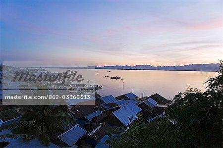 Philippines,Palawan,Puerto Princessa. Sunet over waterfront shanty houses.