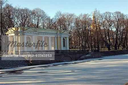 Russland, St. Petersburg. Die Gärten des Palastes Michael. Ein Pavillon am Ufer des Kanals Moika in den Gärten des Palastes Michael, jetzt das russische Museum of Art. Die Kirche auf dem Blut vergossen kann durch die Bäume gesehen werden.