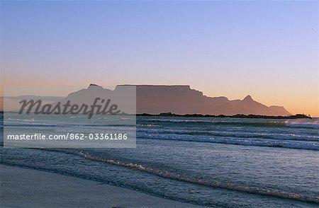 Surf roule sur une plage déserte près de Bloubergstrand à Cape Town et de la montagne de la Table derrière