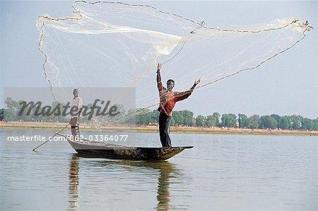 Filets de main de cast pêcheur sur le fleuve Niger de bateaux tirant d'eau peu profonde