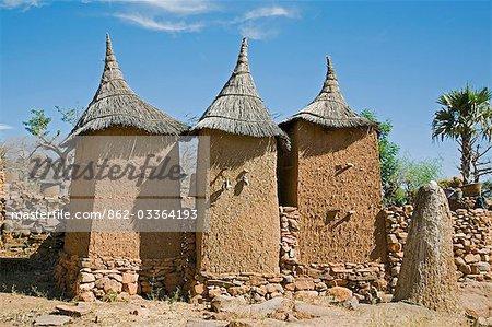 Au Mali, pays Dogon, Koundu. Un petit village construit parmi les rochers près du village Dogon de Koundu. Habitations ont des toits plats alors que les greniers pour stocker millet ont planté des toits de chaume. Les Dogons sont animistes. La butte en terre sacrée à droite avec un œuf d'autruche sur le dessus se trouve un autel utilisé pour les sacrifices par le hogon village ou le prêtre pour apaiser les ancêtres et purifier le village.