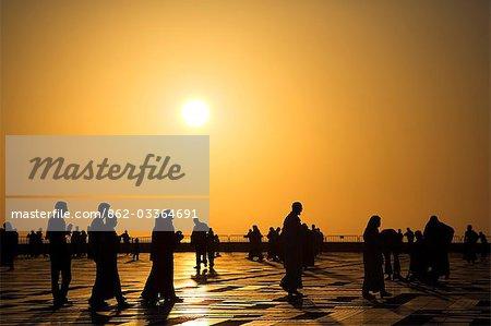 Familles et amis profiter d'une promenade en soirée ou le paseo, sous le soleil couchant dans la Cour de la mosquée Hassan II à Casablanca.