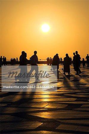 Familles et amis profiter d'une promenade en soirée ou le paseo, sous le soleil couchant dans la Cour de la mosquée Hassan II à Cassablanca.