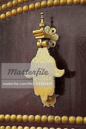 La main de Fatima, sur une porte en bois traditionnelle à la kasbah de Tanger, le point culminant de la ville. La main protège la maison contre le mauvais œil.