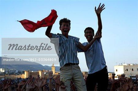 Maroc, Fes. Deux garçons marocaines fière saluent leur drapeau national au-dessus de la foule lors d'un concert à la Place Boujloud, au cours de la Fes Festival de musiques sacrées du monde.