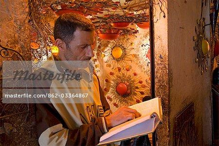 Maroc, Marrakech. Homme lisant le Coran dans les travailleurs de la métallurgie Souk.