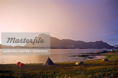 Norvège, Nordland, Helgeland. Le soleil de minuit sur un camp de kayakistes et le pic de Rodoylova, sur l'île de Rodoy