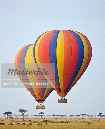 Kenya, Masai Mara, Masai Mara Game Reserve. Deux ballons à air chaud flottent au-dessus des plaines dans la réserve Masai Mara tandis que les troupeaux de gnous paissent ci-dessous.