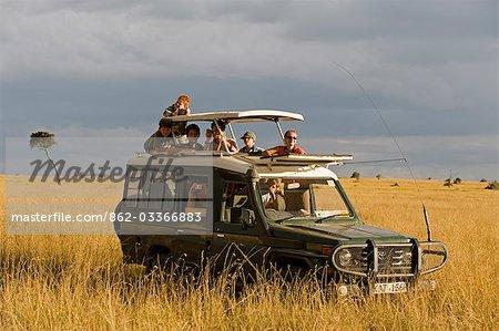 Kenya, Masai Mara National Reserve. Famille sur un safari dans une Toyota Landcruiser dans les plaines herbeuses de Masai Mara.