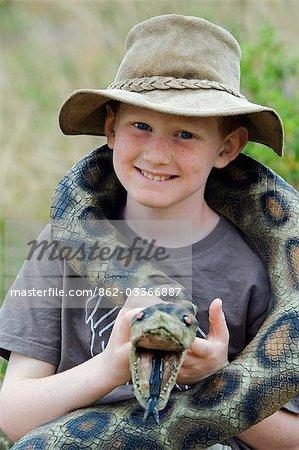 Kenya,Masai Mara National Reserve. Young boy on safari in the Masai Mara playing with a toy snake .