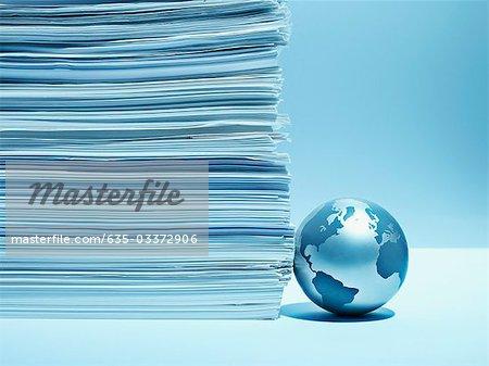 Metal globe against stack of paper