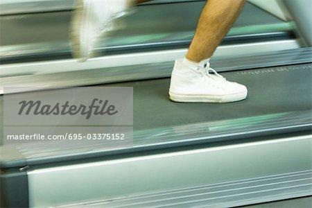 Homme en cours d'exécution sur le tapis roulant, pieds en gros plan