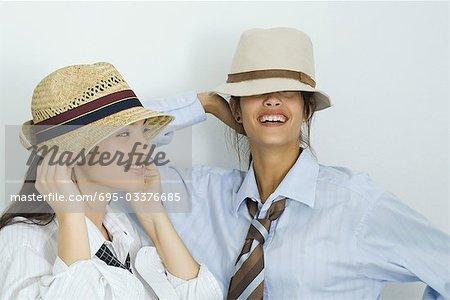 Deux jeunes amis porter un chapeau, sourire aux lèvres, les yeux couverts