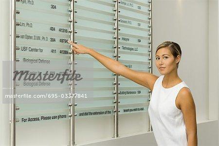 Femme pointant sur le répertoire de construction, en regardant la caméra